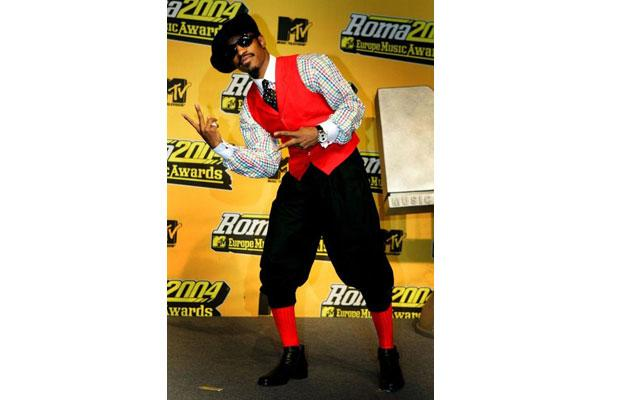 Andre3000 mixing the past with the future with plaid, knickerbockers, and a bright red vest